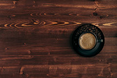 Hot coffee in black cup with crema and beans with copy space on brown old wooden board background, top view. Stock Photography