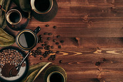 Hot coffee in black cup and several turkish pots cezve with beans, dry leaves with copy space on brown old wooden board background Stock Images