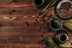 Hot coffee in black cup and several turkish pots cezve with beans, dry leaves with copy space on brown old wooden board background Stock Photography