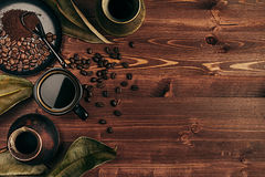 Hot coffee in black cup and several turkish pots cezve with beans, dry leaves with copy space on brown old wooden board background Stock Photo