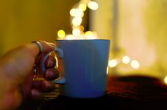 Closeup image of a hand holding white cup of hot coffee with bokeh Backgrounds. Hot coffee with bokeh Backgrounds royalty free stock photography