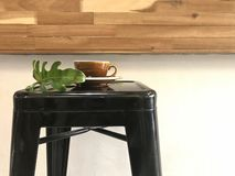 Hot coffee with bottom and green plant part on black bar stool. Brown cup of hot coffee with bottom plate and green plant part on black metal bar stool with royalty free stock photography