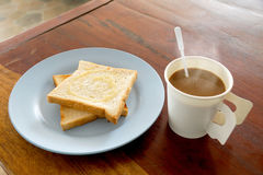 Hot coffee and bread toast topped with milk for breakfast. On wood table royalty free stock photos