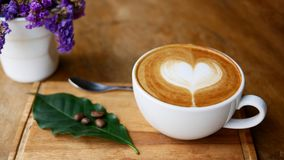 Hot coffee cappuccino latte art heart shape in ceramic cup on wood plate. Decorate with coffee beans on green leaf and purple flower on table background royalty free stock photography