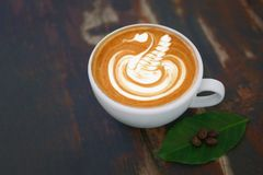 Hot coffee cappuccino latte art swan shape in ceramic cup on woo stock photos