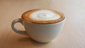 Hot coffee cappuccino latte in ceramic cup with spiral milk foam royalty free stock photos