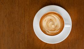Hot coffee cappuccino latte spiral milk foam top view on wooden background royalty free stock photos