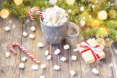 Hot coffee chocolate with marshmallow on rustic wooden table background, candy canes gift boxes fir tree with snow. Hot coffee chocolate with marshmallow in stock images
