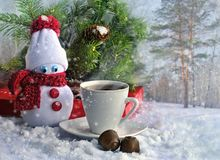 Hot coffee, chocolate and a small snowman in a red scarf on a snowy day Stock Images