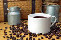 Hot coffee with coffee bean on wooden table. And zinc pots, hamper basket and sack background royalty free stock image