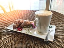 Hot coffee with croissants decorate with flower on rattan table. Hot cappuccino coffee drink with croissants decorate with flower on rattan wood table royalty free stock image