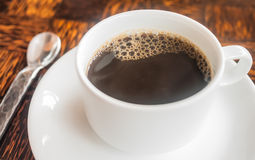 Hot coffee cup. Hot coffee in the white ceramic cup with bubbles Royalty Free Stock Photos