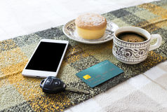 Hot coffee in cup, bakery, credit card, mobile phone and car key Stock Images