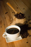Hot coffee cup and bean in bag on wood background vintage tone Royalty Free Stock Photos