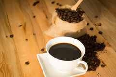 Hot coffee cup and bean in bag on wood background vintage tone Stock Photography