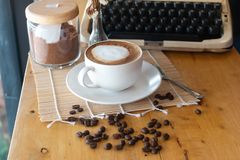 Hot coffee in cup and coffee bean and typewriter royalty free stock images