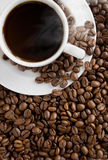 Hot coffee cup on the beans. Coffee cup on the beans. Close up Royalty Free Stock Photo