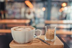 Hot Coffee cup and brown sugar on the wooden tray in coffee shop background. royalty free stock photo