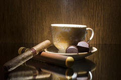 Hot coffee. Hot cup of coffee , cigar and two chocolate candies stock photo
