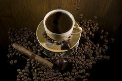 Hot coffee. Hot cup of coffee , cigar and two chocolate candies stock photography
