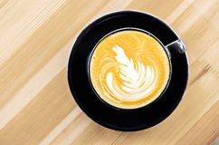 Hot coffee in a cup with foam milk beautiful latte art. On wooden background royalty free stock photography