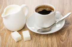 Hot coffee in cup, jug of milk, sugar, spoon. On wooden table Royalty Free Stock Photo