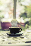 Hot coffee in the cup on morning background. Royalty Free Stock Image