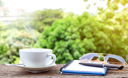 Hot coffee cup  with a notebook, sunglasses and pen. Royalty Free Stock Photo