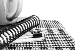 Hot Coffee Cup and Notebook on Wooden Mat, black and white photo Royalty Free Stock Photo