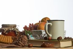 Hot coffee cup old book glasses and autumn leaves with fruit basket stock photo