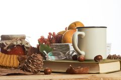 Hot coffee cup old book glasses and autumn leaves with fruit basket royalty free stock photography