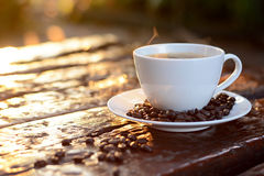 Hot coffee in the cup on old wood table with coffee beans Stock Photography