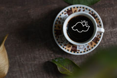 Hot coffee in the cup on old wood table with leaf Royalty Free Stock Image