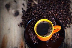 Hot coffee. Cup of hot coffee on plate with coffee beans, close-up Royalty Free Stock Photography