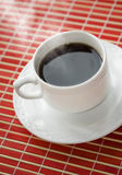 Hot coffee cup on the red mat. Close up. Coffee cup on the mat. Close up Royalty Free Stock Image