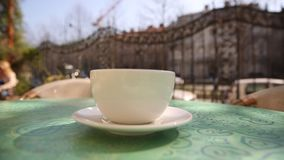 Hot coffee cup with steam on table in cafe in the morning, outside stock footage