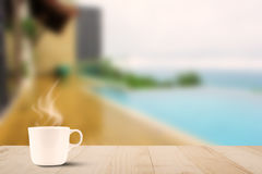 Hot coffee cup with steam on wooden table on blurred pool and se Stock Images