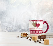 Hot coffee cup and sweets over frosted winter background Royalty Free Stock Photos