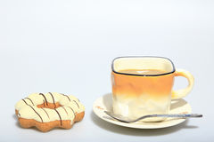 Hot coffee in the cup with white chocolate donuts, as foods background. Stock Image
