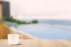 Hot coffee cup on wooden table on blurred pool and sea background Stock Photography
