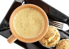 Espresso hot coffee with milk in brown ceramic cup and banana cupcakes on black dish, beverage and sweet dessert for coffee break. Flat lay close-up top view of Stock Photo