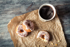 Hot coffee and donuts given in the paper. On old wooden table stock images