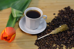 Hot coffee drink, flower, sugar stick and coffee beans Royalty Free Stock Photo