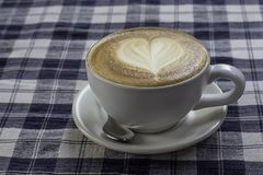 Hot coffee Espresso topped with a heart-shaped milk in white glass On the table with chintz Scott stock photography
