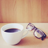 Hot coffee and eyeglasses with retro filter Stock Image