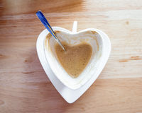 Hot coffee fade and spoon in white heart cup. On wooden table Stock Photo