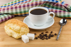 Hot coffee, flaky biscuits and sugar cubes on table Stock Photos