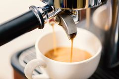 Hot coffee flowing into a cup from machine. Coffee making, hot coffee flowing into a cup from espresso machine Stock Photography