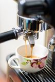 Hot coffee flowing into a cup from machine. Coffee making, hot coffee flowing into a cup from espresso machine Stock Images
