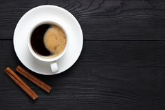 Hot coffee with foam in a white cup with cinnamon and place under the text Stock Photography
